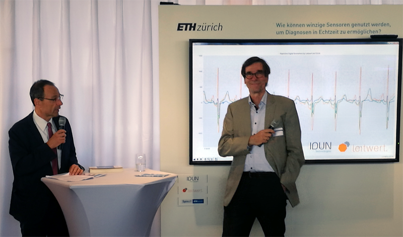 fotograph of former ETH President Prof. Dr. Lino Guzzella and Prof. Dr. Lothar Thiele during the inaugural address in front of the live ECG stream delivered by the Leitwert Device Hub